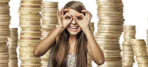 Studentin steht vor einem Stapel Geld, macht große Augen