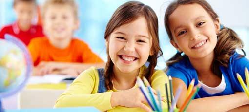 Zwei Kinder sitzen im Unterricht und freuen sich