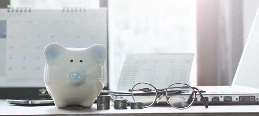 Sparschwein steht auf einem Schreibtisch mit gestapelten Münzen