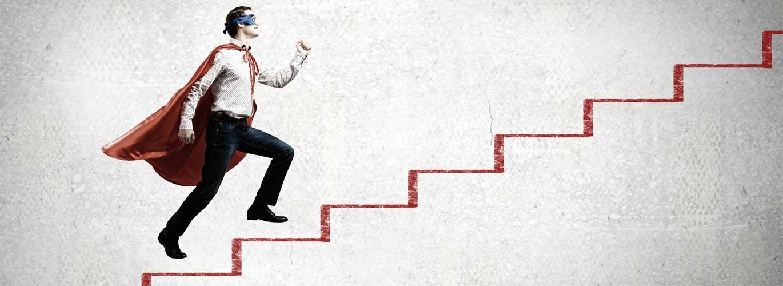 Karrierechance: Erziehungsberater - Mann mit Supermanumhang rennt eine Treppe hoch