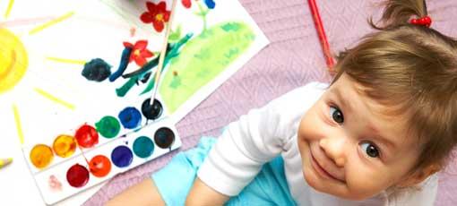 Kind spielt auf dem Boden mit Wasserfarben