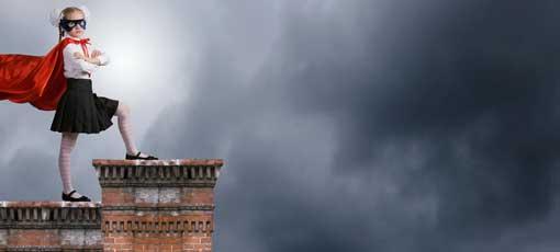 Kind verkleidet als Superheldin steht auf einem Dach