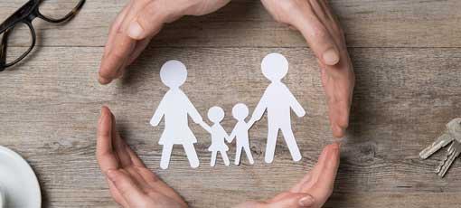 Vier Hände schützen eine Familie