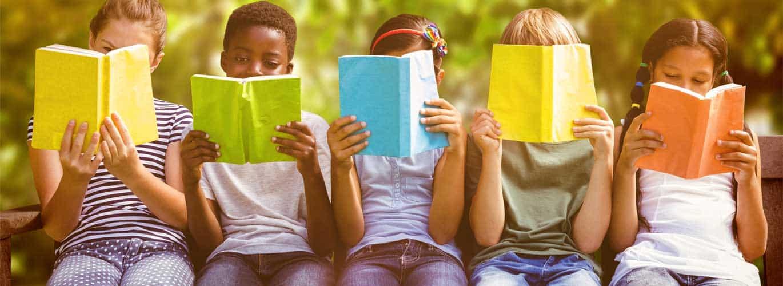 Kindergaertnerin - Kinder lesen in einem Buch