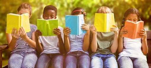 Kinder lesen ein Buch im Freien