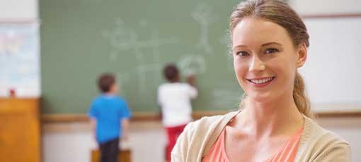 Lernberaterin steht in einem Klassenzimmer mit Kindern