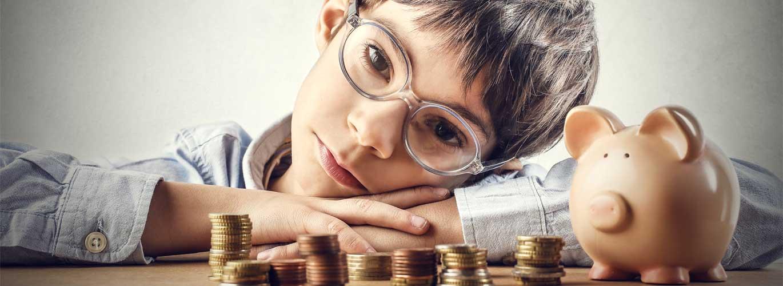 Taschengeld Kinder - Kind sitzt neber seinem Sparschwein