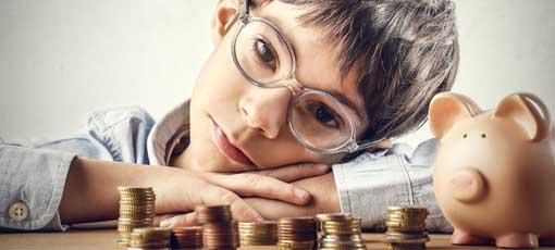 Kind sitzt bei seinem Sparschwein vor einem Stapel Münzen