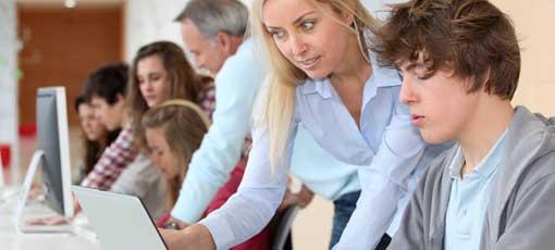 Weiterbildungspädagogin unterstützt Auszubildende am Notebook