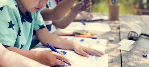 Kinder malen zusammen an einem Tisch