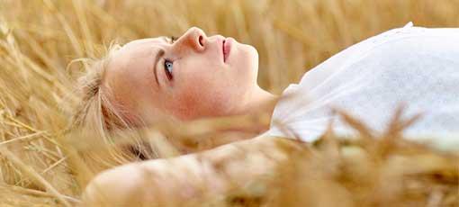Nachdenkliche Frau liegt im Getreidefeld