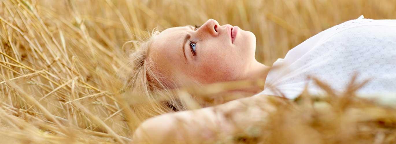 Sozialmanagement - Frau liegt in einem Getreidefeld