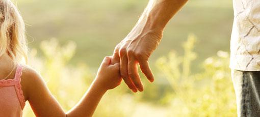 Junges Mädchen hält die Hand eines Erwachsenen
