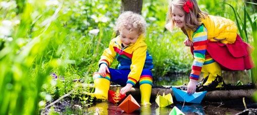 Kinder spielen in der Natur an einem Bach