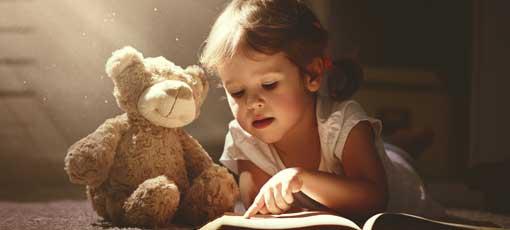 Kind ließt ein Kinderbuch mit Ihrem Teddy